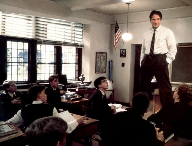 Robin Williams standing on desk in front of classroom of boys